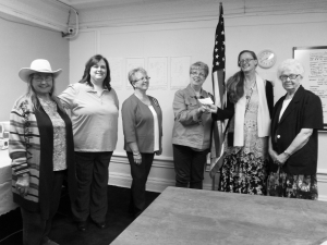 DAR members (l to r) Melanie Funcannon, Lori Mann, Patty Kinder, and Pam Russell present A. R. Mitchell Museum Director Christina Boyce with a memorial contribution in honor of the late Paul Cordova, a past director of the museum, as his wife Roberta (rt) looks on.  The 48 star flag in background was donated to the museum by Mrs. Cordova.  Photo by Joy Gipson.