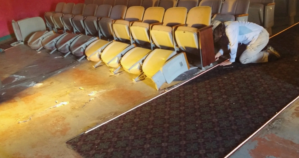 Improvements continue at Walsenburg's Fox Theatre.  Last week volunteers removed the first three rows of seats at the historic Fox theatre in preparation for the installation of a dance floor.  The area cleared of seats will be leveled with a subfloor, then eventually covered with hardwood.  The master plan for the Fox is to turn the historic building into a multipurpose performance hall.  Pictured is volunteer Edie Flanagin, helping pull the seats from the floor.  Photo by Bo Sewell.