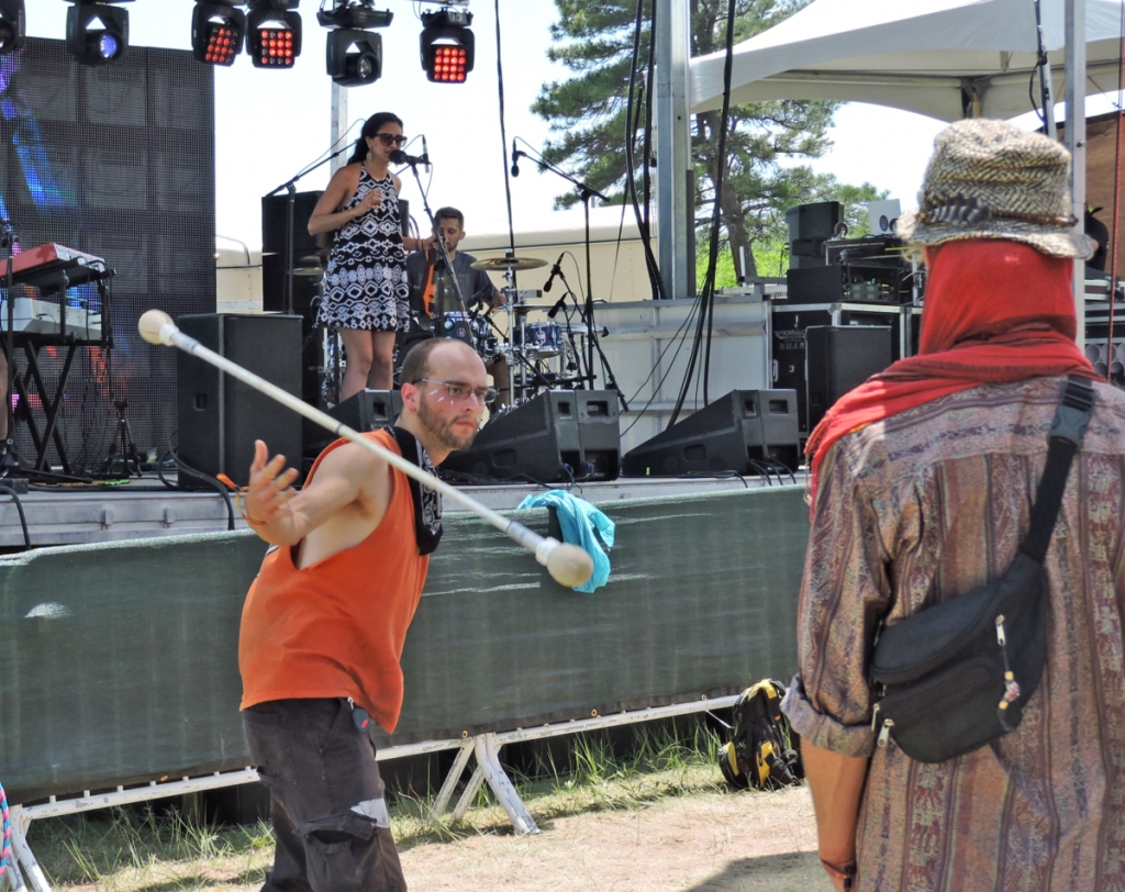 Man shows off magical levitating stick to amazed concert-goer.